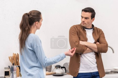 mad adult couple having argument at kitchen
