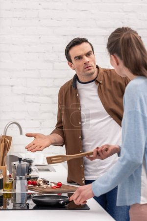 adult couple having argument at kitchen suring while preparing dinner