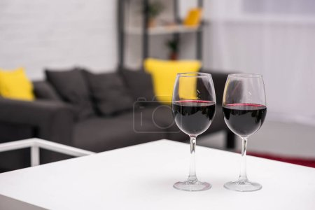 close-up shot of red wine on table in front of blurred living room on background