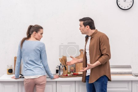 Photo for Side view of adult couple having argument at kitchen - Royalty Free Image
