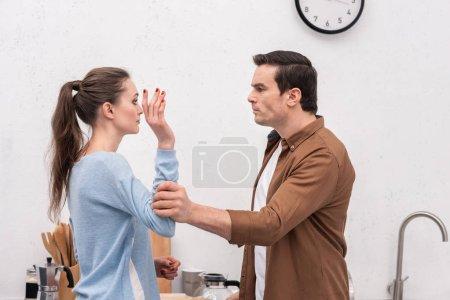 Photo pour Fou homme tenant la main de femme lors de dispute à la cuisine - image libre de droit