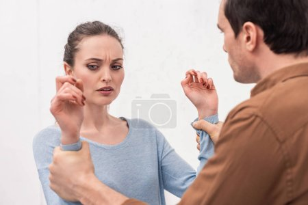 angry man holding hands of woman during argument