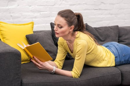 focused adult woman reading book on couch at home