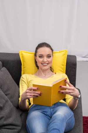 happy adult woman reading book on couch at home and looking at camera