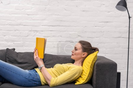 side view of adult woman reading book while lying on couch at home