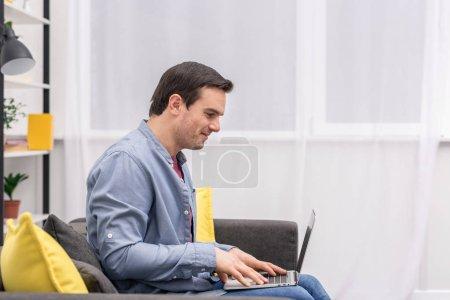 Photo pour Vue latérale de bel homme adulte utilisant un ordinateur portable sur le canapé à la maison - image libre de droit