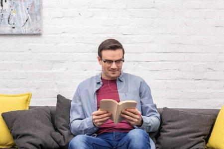 Photo pour Heureux adulte livre de lecture sur canapé à la maison en face du mur de briques blanches - image libre de droit