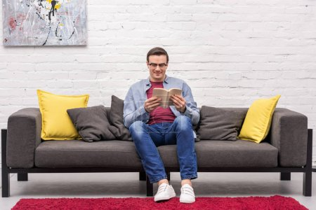 happy adult man reading book on sofa at home