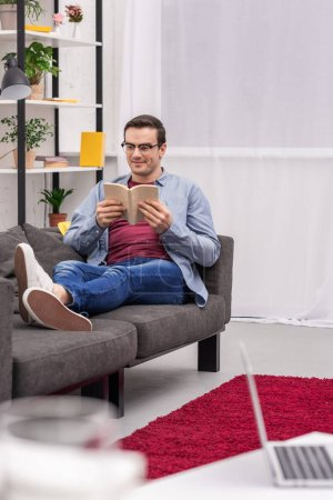 smiling adult man reading book on couch at home