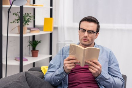 concentrated adult man reading book on couch at home