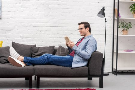side view of happy adult man reading book on couch at home