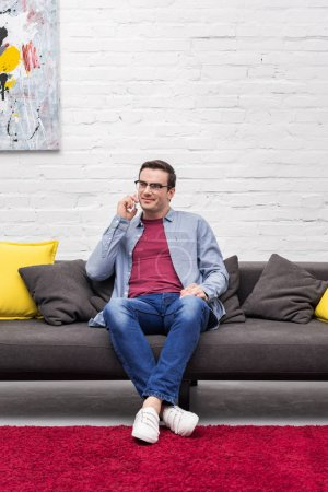 smiling adult man talking by phone on couch at home