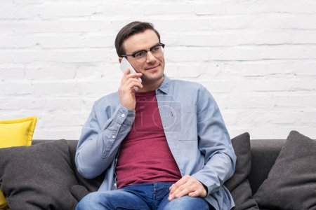 happy adult man talking by phone on couch at home
