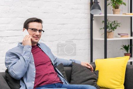 bel homme adulte parler par téléphone sur canapé à la maison