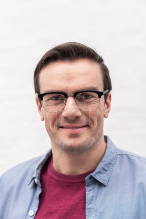 close-up portrait of smiling adult man in eyeglasses looking at camera in front of white wall