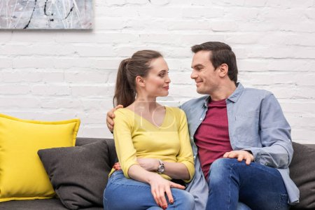 beautiful adult couple sitting on couch at home and looking at each other happily