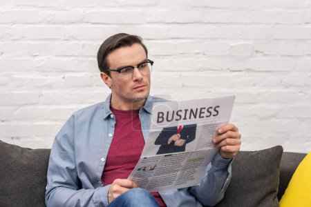 concentrated adult man reading business newspaper on couch at home
