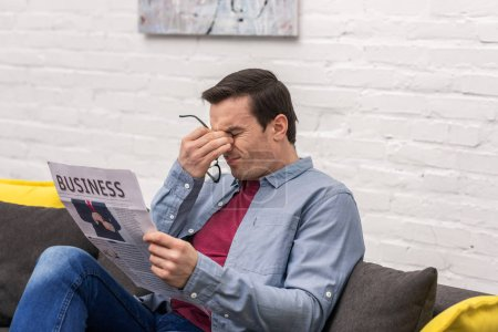 tired adult man rubbing eyes while reading newspaper
