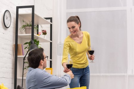 smiling adult woman giving glass of wine to her boyfriend at home