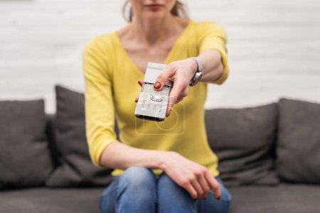 Photo pour Recadrée tir de femme adulte avec télécommande regarder la télévision tout en étant assis sur le canapé - image libre de droit