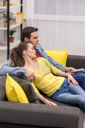 beautiful adult woman sleeping on shoulder of her boyfriend while he sitting on couch with tv remote control