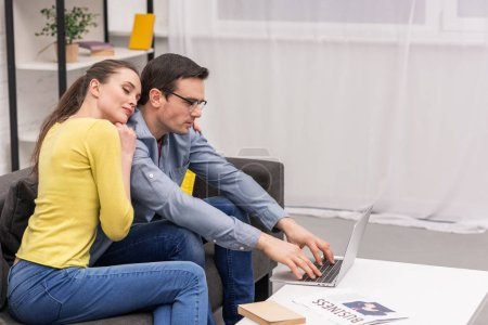 Photo for Beautiful adult couple leaning on her husband while her working with laptop on couch at home - Royalty Free Image