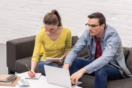 confident adult couple of freelancers working on couch at home together