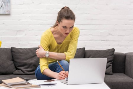 Photo for Serious adult woman working with laptop at home on couch - Royalty Free Image