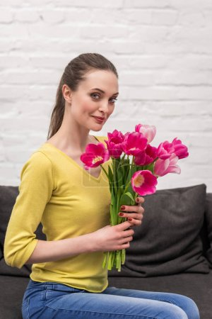 attractive adult woman holding pink tulips bouquet and looking at camera