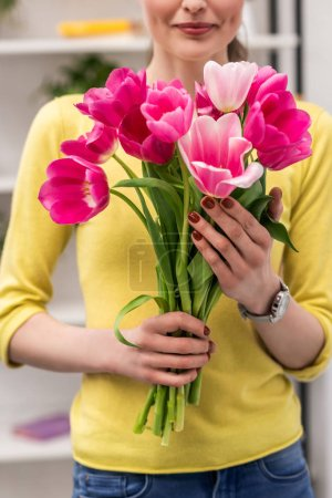 cropped shot of adult woman holding pink tulips bouquet