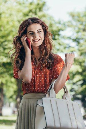 portrait of smiling beautiful woman talking on smartphone on street
