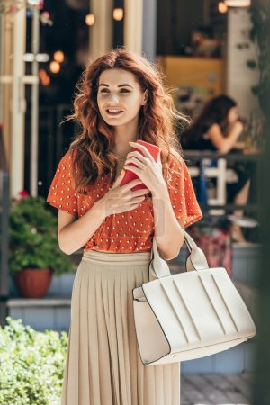portrait of young woman in stylish clothing with smartphone and bag on street