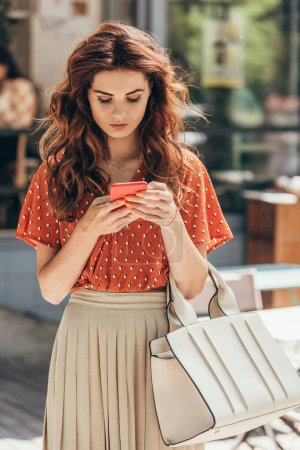 portrait of young stylish woman using smartphone on street