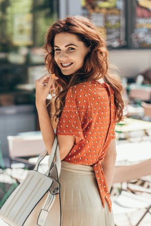 side view of young smiling woman in stylish clothing on street