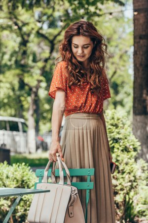 portrait of young woman in stylish clothing putting bag on chair on street