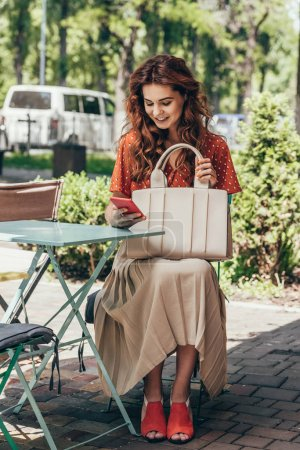 stylish woman with bag using smartphone while sitting on terrace in cafe