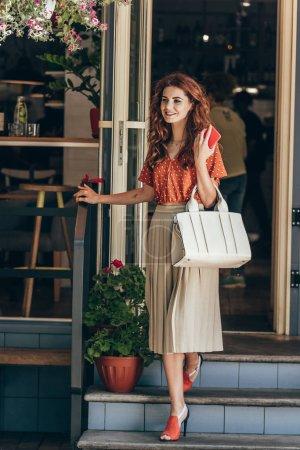 Photo pour Femme élégante avec smartphone et sac promenade café - image libre de droit