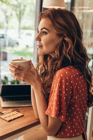 side view of pensive woman with cup of coffee at table with laptop in cafe