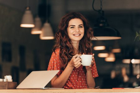 Photo for Portrait of smiling woman with cup of coffee at table with laptop in cafe - Royalty Free Image