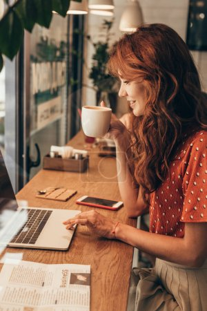 Photo for Side view of young blogger with cup of coffee working on laptop in coffee shop - Royalty Free Image