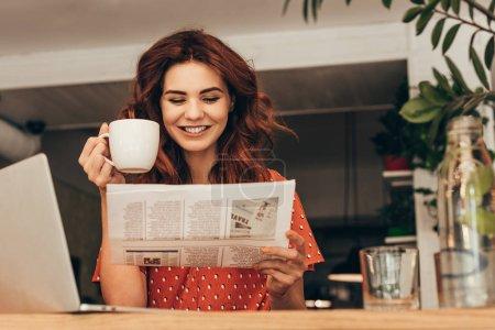 Photo pour Portrait de femme souriante avec une tasse de café en lisant le journal à table avec l'ordinateur portable dans le café-restaurant - image libre de droit