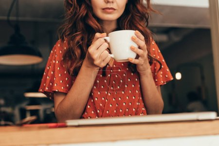 cropped shot of woman with cup of aromatic coffee in hands in cafe