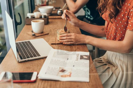 partial view of woman eating souffle at table with laptop in coffee shop