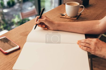 cropped shot of blogger making notes in notebook at table with cup of coffee in coffee shop