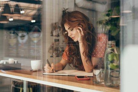 Photo pour Jeune blogueur, prendre des notes dans l'ordinateur portable à table par tasse de café en café-restaurant - image libre de droit