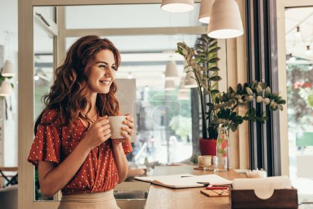 smiling young woman holding cup of coffee at table with notebook in cafe