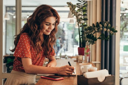 side view of young blogger making notes in notebook at table with cup of coffee in coffee shop