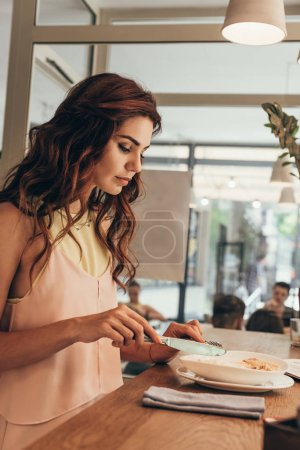 side view of young woman eating italian pasta in cafe