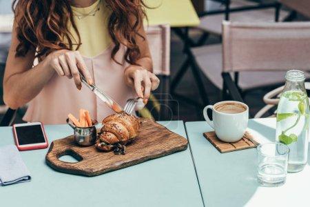 cropped shot of woman having breakfast alone in cafe
