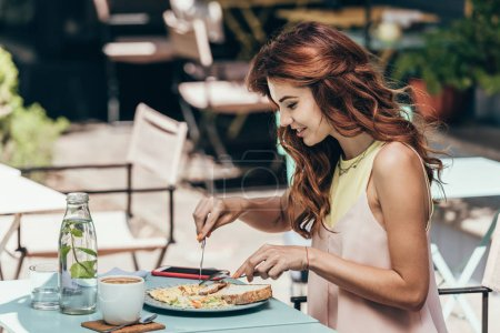 side view of young woman having lunch alone in restaurant
